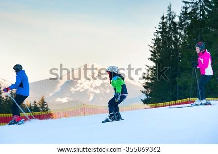 BUKOVEL, UKRAINE - DEC 08, 2015: Family skiing in Bukovel. Bukovel is the most popular ski resort in Ukraine. - stock photo