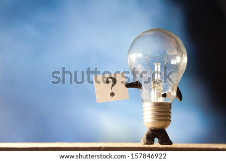 Bulb holding a poster with question mark. - stock photo
