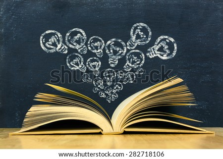 Bulbs symbol above vintage old book on blackboard background