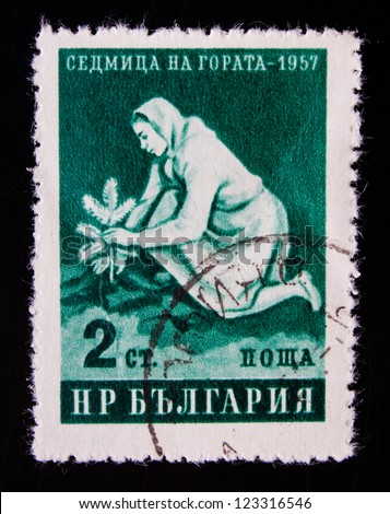 BULGARIA - CIRCA 1957: A stamp printed in Bulgaria shows a woman with a plant in the forest at night, circa 1957.