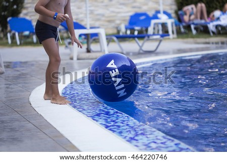 BULGARIA, JULY 29, 2016: Boy plays with NIVEA inflatable ball floating on water. NIVEA is a German personal care brand specialized in skin and body-care owned by Beiersdorf Global AG.