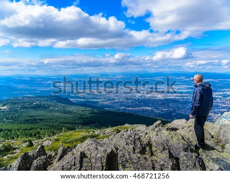 Bulgaria, Sofia, Vitosha mountain - person standing on a mountain top, looking towards the city in the distance
