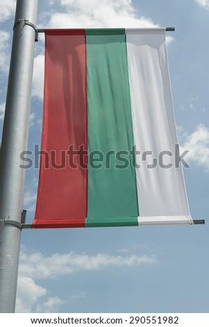 Bulgarian flag on a pylon against blue sky  - stock photo
