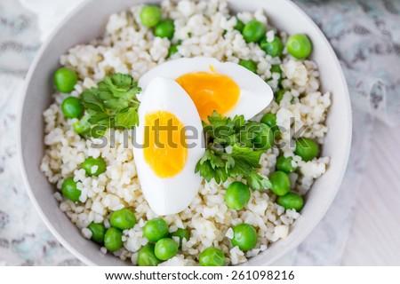 Bulgur, rice with green peas, boiled egg yolk, spring, summer - stock photo