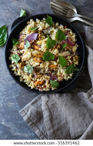 bulgur with mussels in pan, above - stock photo