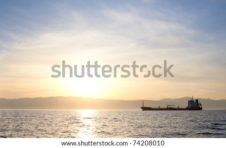 Bulk-carrier ship at sunset in the sea