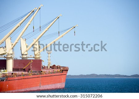 Bulk carrier ship with cranes anchoring at loading terminal of port, with ocean water, coast at horizon, blue sky, copy space. - stock photo
