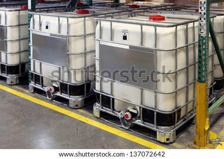 Bulk fluid shipping containers on pallets in a warehouse, ready for shipment - stock photo