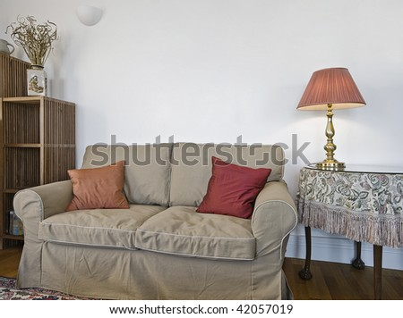 bulky sofa with round side table and reading lamp