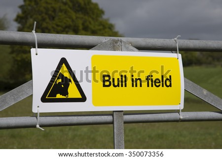 Bull in field warning sign attached to farm gate England UK