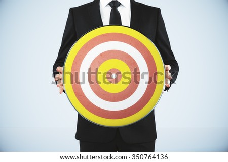 Bull's-eye concept with businessman holds a dart - stock photo