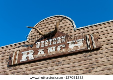 bull skull and western ranch board on a wooden facade - stock photo