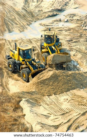 Bulldozer and a lorry load sand on district - stock photo