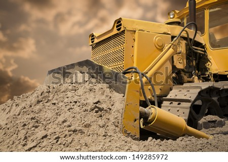Bulldozer at work on the orange sky background - stock photo
