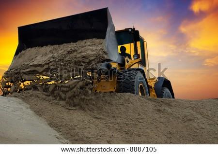 Bulldozer at work with sunset background - stock photo