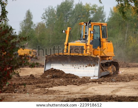Bulldozer attain to level soil at construction site