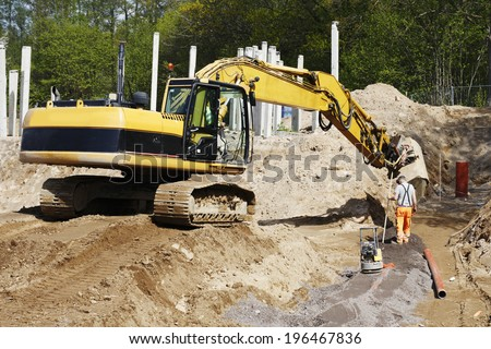 bulldozer, digger and site worker in action, road-works industry and constructions - stock photo
