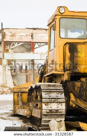 Bulldozer in front of destroying industrial building