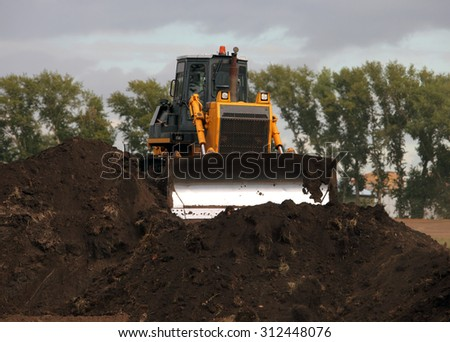 Bulldozer in operation moving dirt and clearing the land