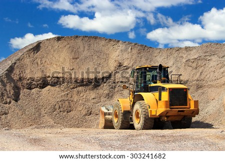 Bulldozer in sand and gravel  site with cloudy blue sky - stock photo