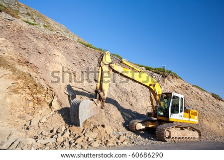 Bulldozer or excavator, industrial machinery against the blue sky - stock photo