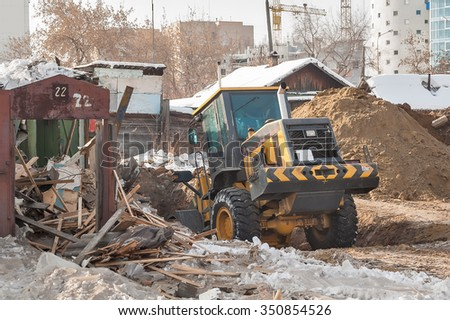 Bulldozer removes debris from demolition of old derelict buildings
