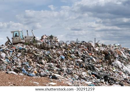 Bulldozer working on mountain of garbage in landfill - stock photo
