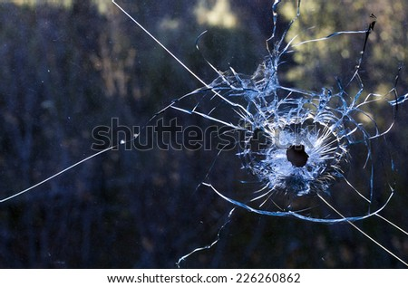 Bullet hole in a dirty glass window - stock photo