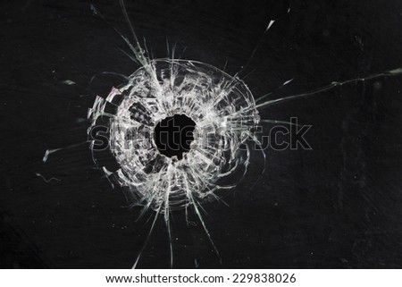 bullet holes in glass isolated on black - stock photo
