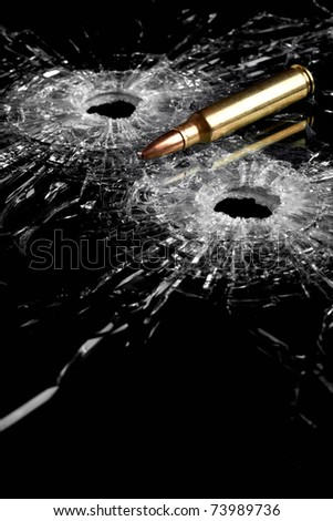 bullet holes in glass with bullet - broken glass isolated on black - stock photo