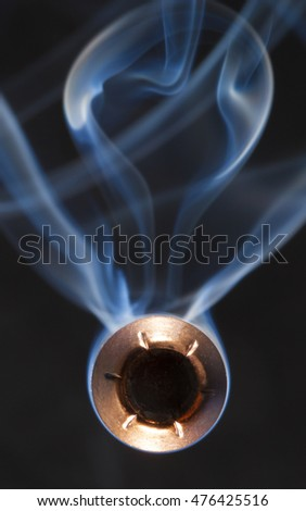 Bullet with a hollow point and smoke that appears to be coming at the camera