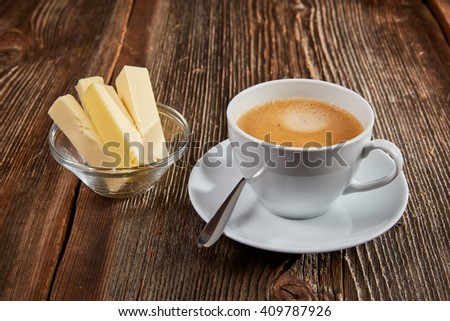 Bulletproof coffee in white cup with butter and coconut oil on a wooden table