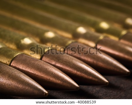 bullets in a row on the wooden surface, closeup shot,shallow DOF with focus on the second bullet, useful for themes such as war,terrorism,crime... - stock photo