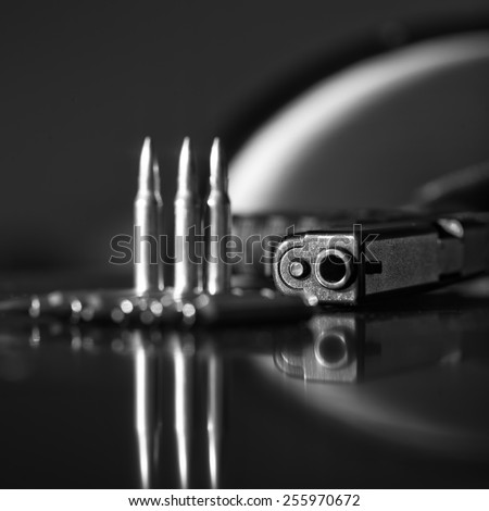 Bullets on a table with a gun barrel in the blurred background, indoor square shot with shallow depth of field, black and white image - stock photo