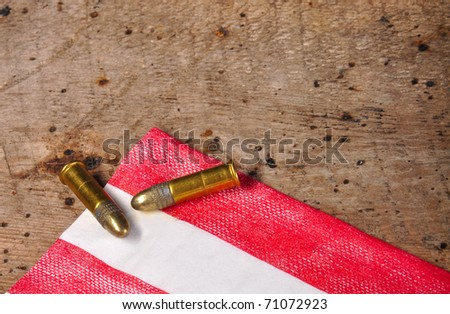 Bullets on old vintage wood table and red and white flag with copy space - stock photo