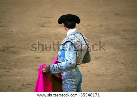 bullfighter waiting with their hands in the cape - stock photo