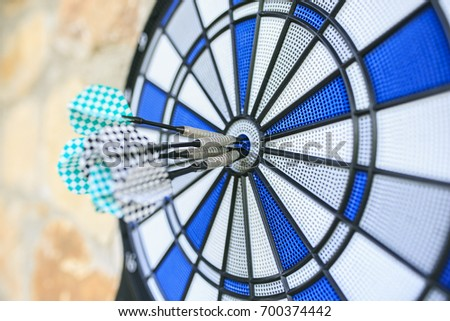 Bullseye on a wall with some darts