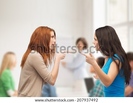 bullying, education, friendship and people concept - two teenagers having a fight at school - stock photo