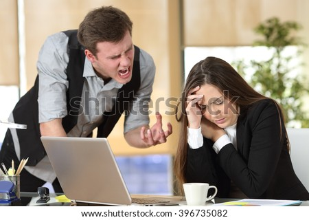 Bullying with an out of control boss shouting to a stressed employee in a desktop at office interior - stock photo