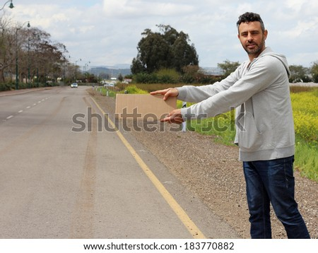 Bum stand on the side of the road wating for a car to hitchhike him - stock photo