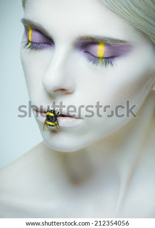 Bumblebee: model with creative make-up and bug on her lips. Large size - stock photo