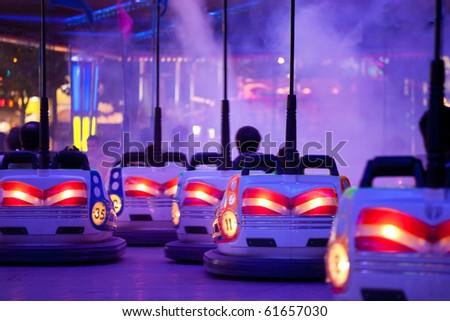 Bumper cars, People driving through artificial smoke. Motion blur - stock photo