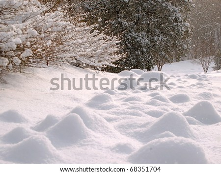 Bumps of snow form on the snow covered ground - stock photo