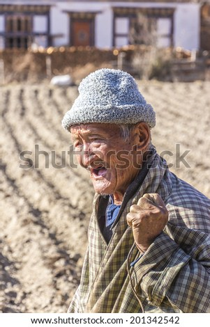BUMTHANG, BHUTAN - MARCH 6, 2014: An old bhutanese farmer is standing on his field, shouting. He is wearing a traditional bhutanese costume.