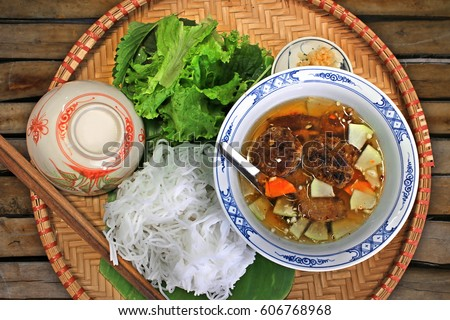 Bun Cha - Vietnamese cuisine: Grilled pork with tasty fish sauce, rice noodles and herbs on a bamboo tray
