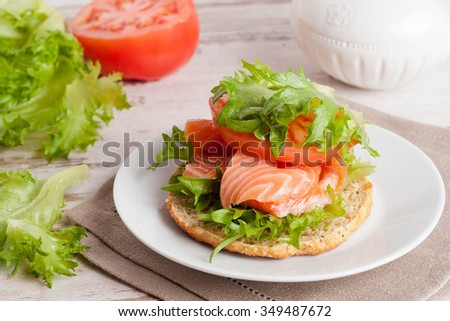 bun with cottage cheese, herbs, tomato and salmon, horizontal, close up - stock photo