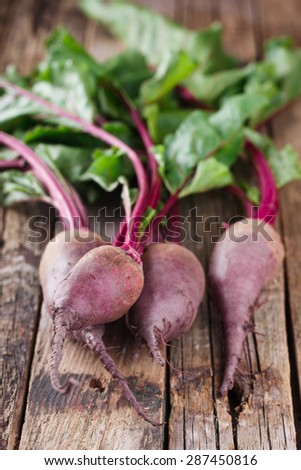 Bunch of Baby Beets with foliage, on wooden background. selective focus - stock photo
