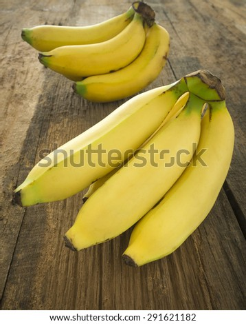 Bunch of bananas ripe placed on a wooden table. - stock photo