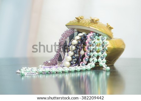 Bunch of beaded jewelry in a vase - stock photo