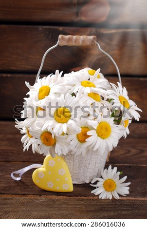 bunch of beautiful fresh daisies in bucket and yellow heart on wooden background